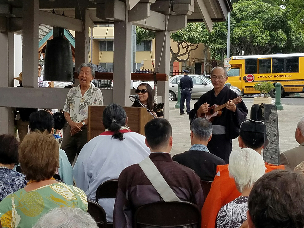 "Photo of From left: Roy Sakuma, Nelly Toyama-Baduria and Consul General of Japan Yasushi Misawa conclude the 27th Annual Hiroshima Commemoration and Peace Service with their 'ukulele rendition of ""I Am What I Am."""