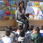 Photo of figure skating champion, Kristi Yamaguchi, reading to a crowd of children