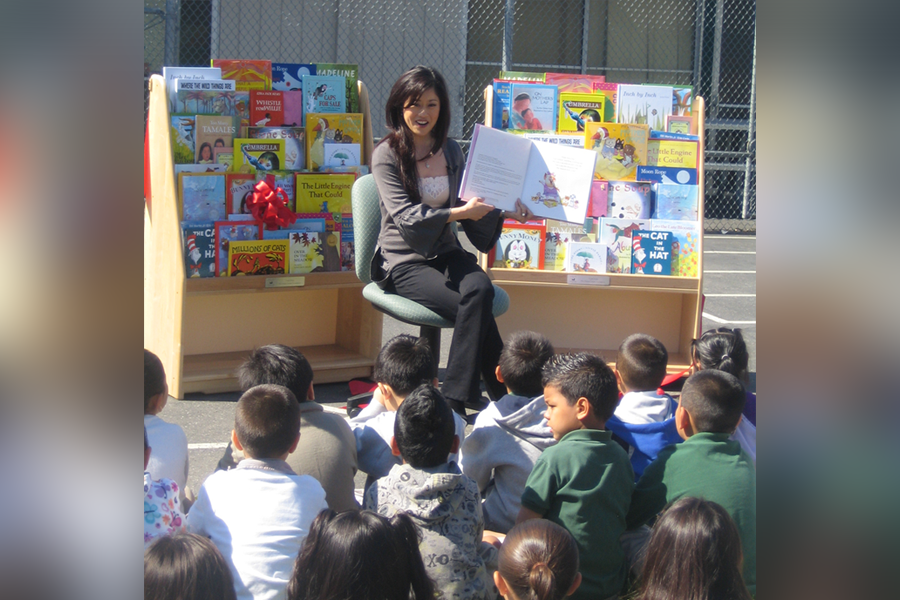 Photo of figure skating champion, Kristi Yamaguchi, reading to a crowd of children