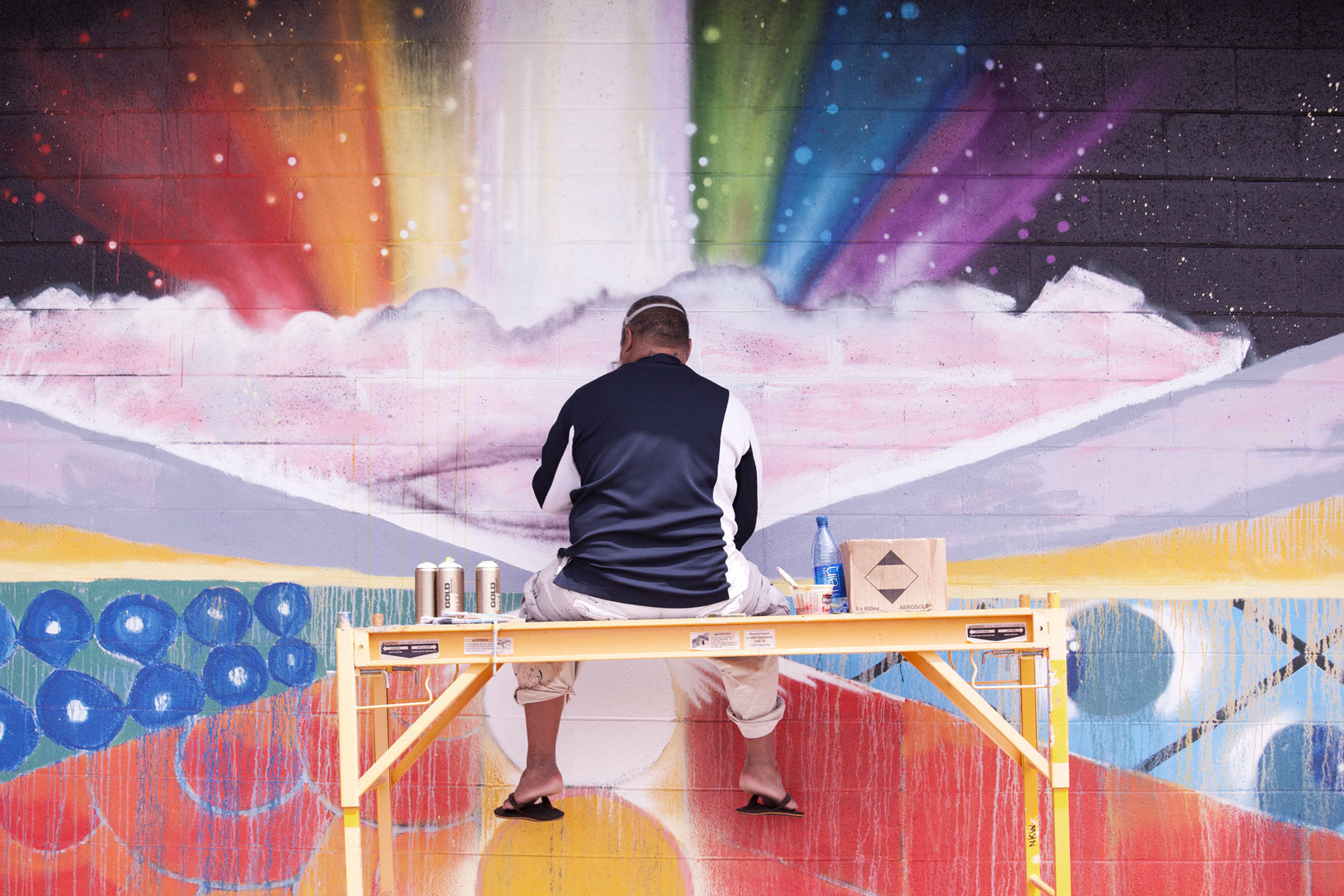 "Photo of John ""Prime"" Hina at work on a mural."