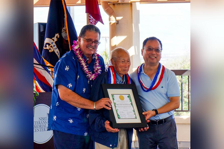 Photo of Maui County Councilman Mike Victorino presents a certificate to Hiroshi Arisumi (center) and Brian Moto, representing the Maui AJA Veterans, Inc.