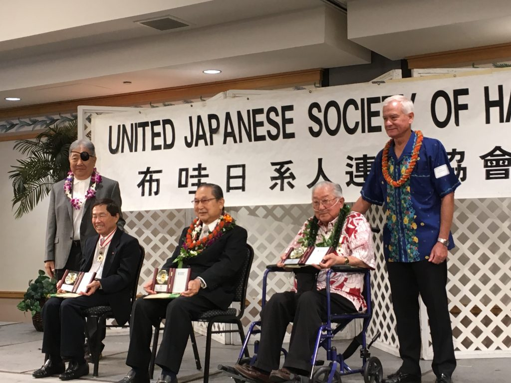 Photo of the United Japanese Society of Hawaii president Dean Asahina (standing, far left) and Honolulu Mayor Kirk Caldwell with Imperial Decoration recipients (seated, from left) Dr. Dennis Ogawa, Joichi Saito and Garrett Serikawa.