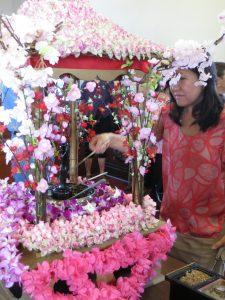 Photo of lady celebrating Hanamatsuri with flower display
