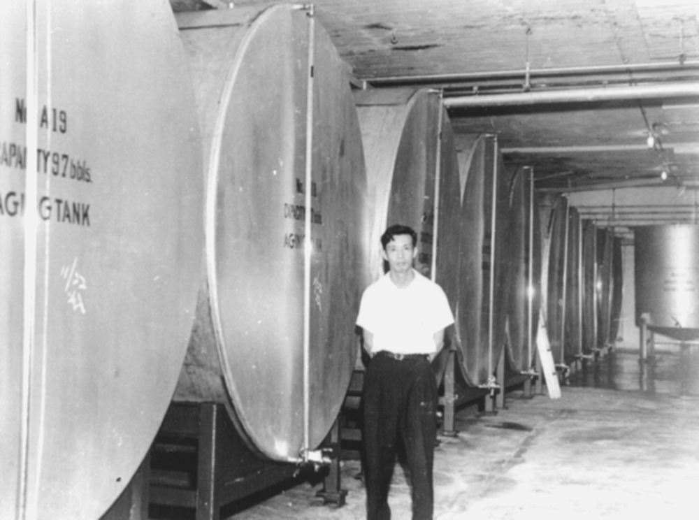 Nihei-san next to a row of sake tanks in the brewery's storage room.
