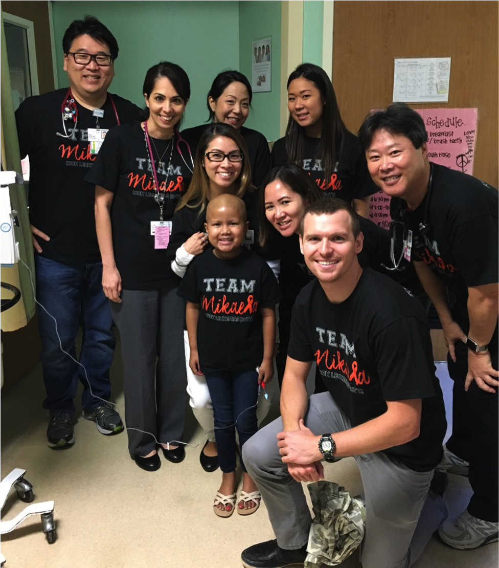 """Team Mikaela! Mikaela with her Kapi'olani medical team — and """"Go Mikaela!"""" team — just before being discharged after receiving a haplo-identical bone marrow transplant from her father. Back row, from left: pediatric oncologist Dr. Wade Kyono, pediatric oncology nurse practitioner Dee Ann Omatsu, pediatric bone marrow transplant coordinator Lori Kaneshige and nutritionist Lauren Yasui. Front row, from left: clinical pharmacist Kristi Itagaki, Mikaela, pediatric oncology hospitalist Dr. Kelley Chinen-Okimoto, pediatric intern Dr. Robert Hagbom and pediatric oncologist Dr. Randal Wada."""