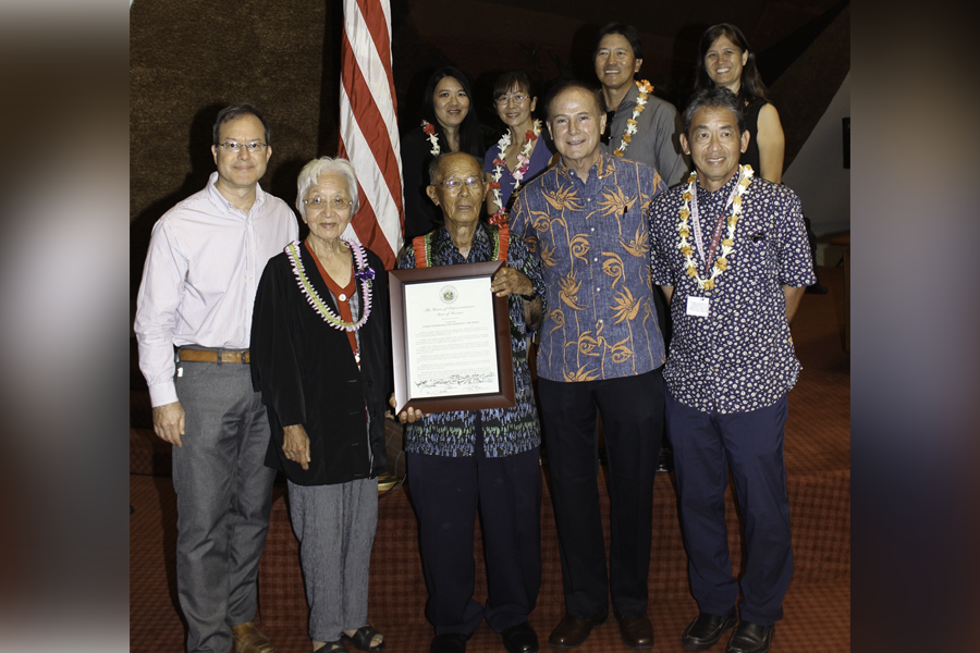 Group photo of McKinley Car War founder Yukio Yoshikawa, state reps, and his family recognizing Yukio for his contributions to Oahu's small business community