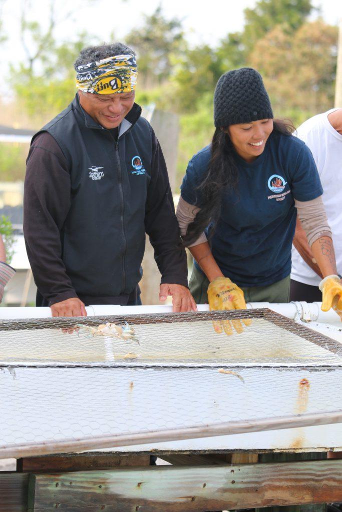 Photo of Kala and her dad, Kalepa Baybayan, working on the canoe