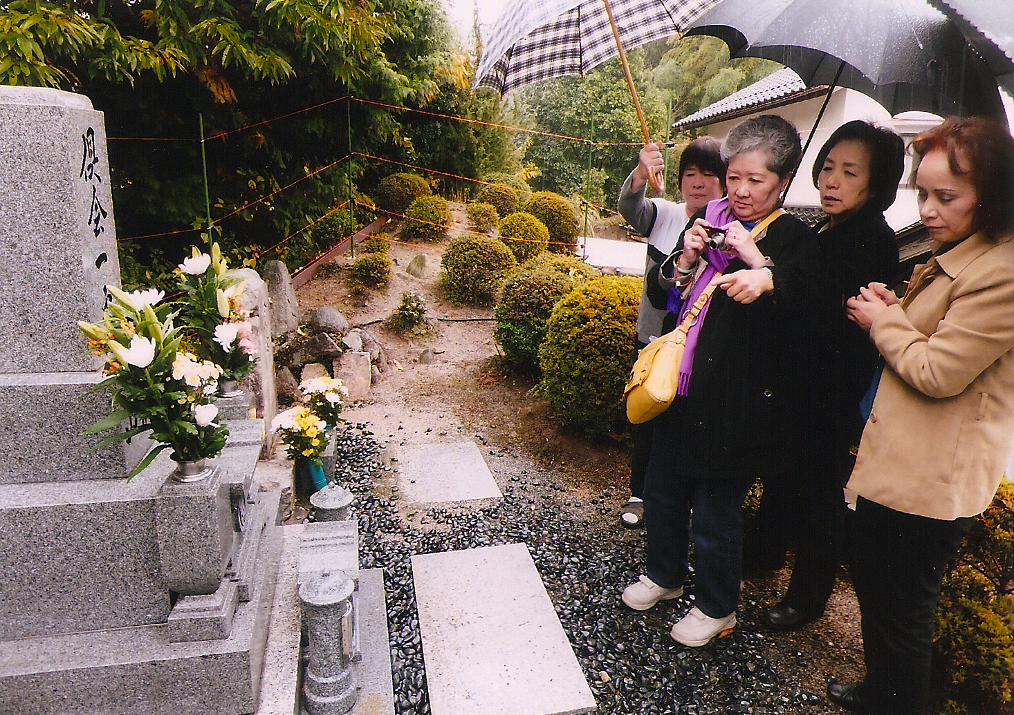 Photo of Lorraine Mito (holding camera) visits her Yamane family ohaka in Hiroshima. (Photos courtesy Lorraine Mito)