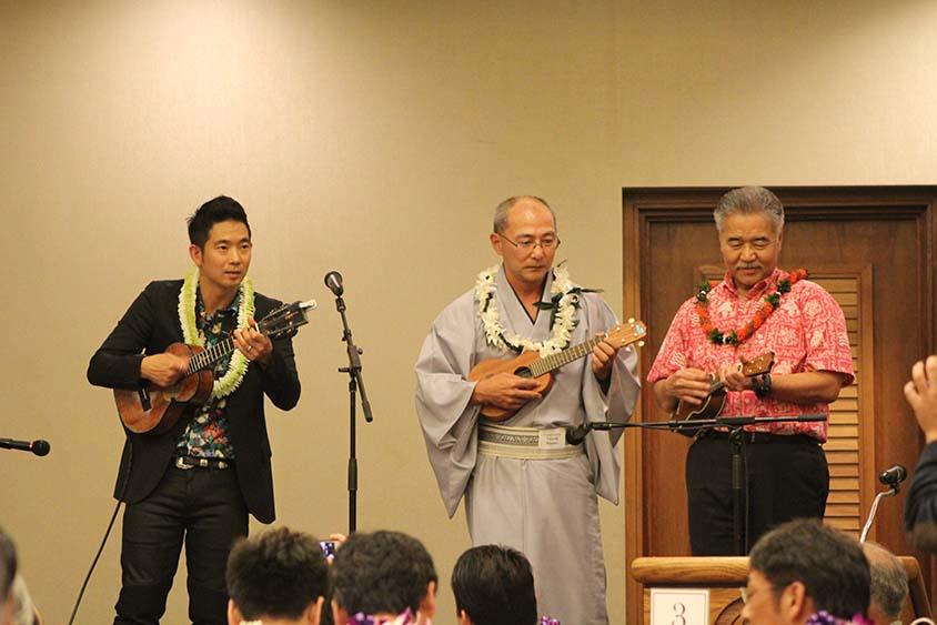 """Photo of 'Ukulele virtuoso Jake Shimabukuro plays """"Wipe Out"""" with Consul General Yasushi Misawa and Gov. David Ige."""