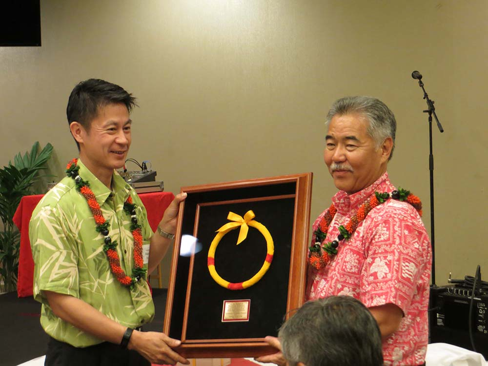 Photo of Gov. David Ige presents a framed feather lei to Hiroshima Gov. Hidehiko Yuzaki.