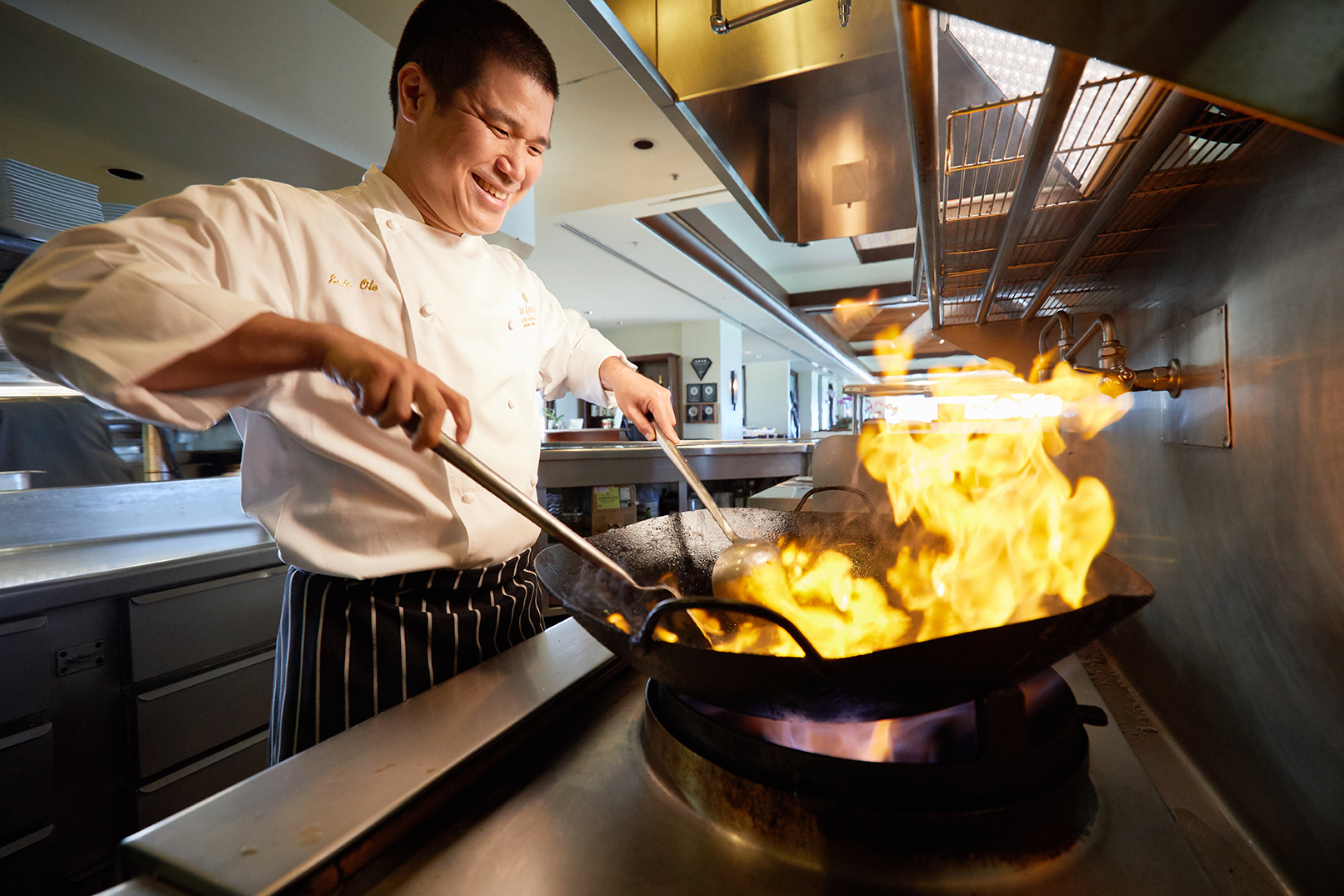 Photo of chef, Eric Oto over a flaming wok