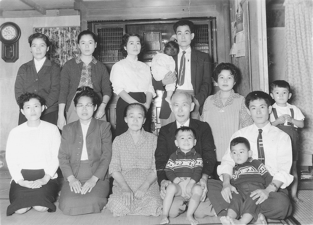 Mom (front row, second from left) made her first trip to Okinawa to visit her mother and her family in 1960 — three decades after she left the island as a child of 12. Front row, from left: Half-sister Kikue Kuwae, Kiyoko Chinen, Mom's mother and her husband, Mom's half-brother Kenyei Arata holding my brother Carlton, then almost 2 years old. Back row, standing: half-sisters Yoshi Fukuhara and Kiyoko Fukuhara, Keiko and half-brother Tamotsu Arata, and half-sister (kneeling) Chiyo Takushi.