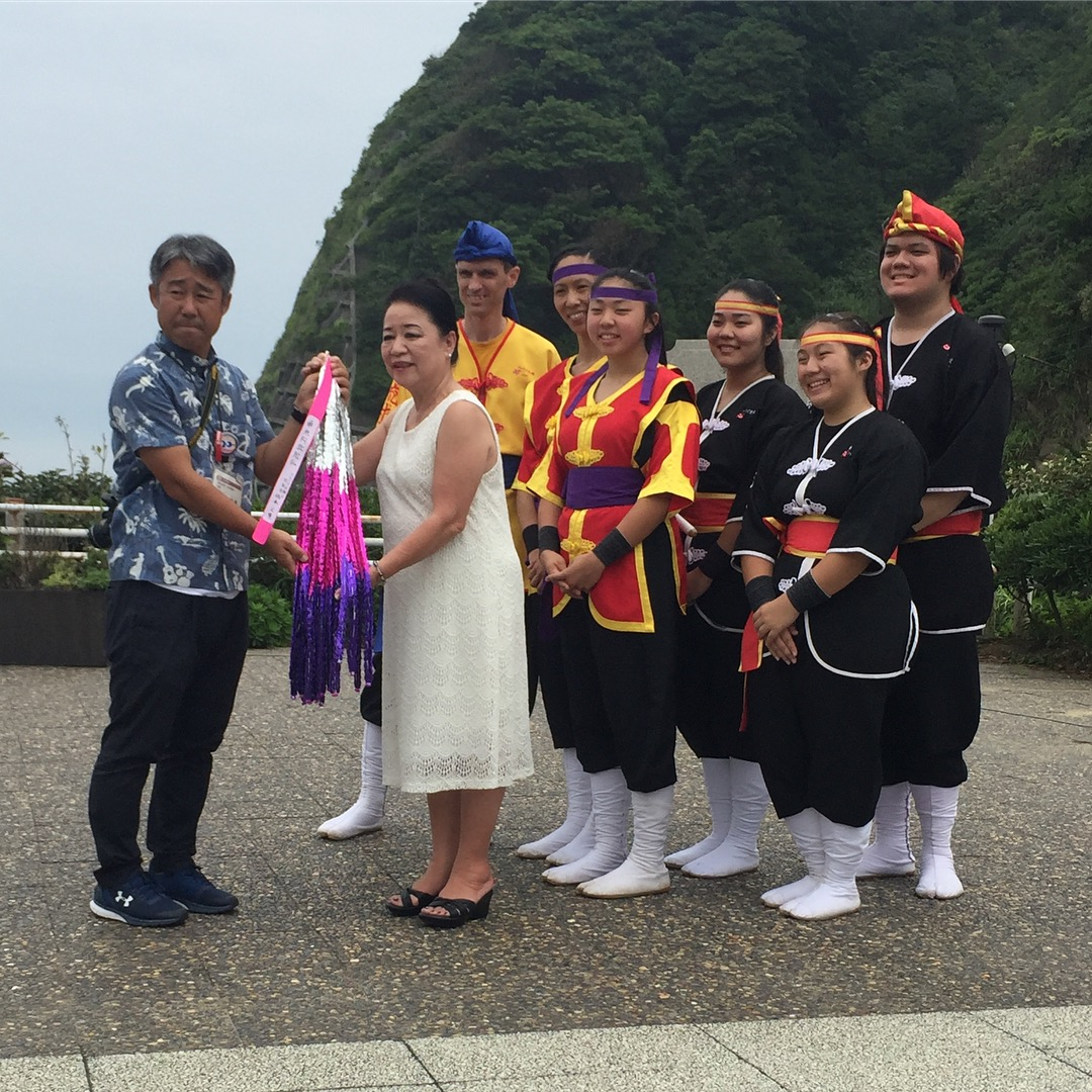 Akemi Martin-Sensei presents the senbazuru (1,000 origami cranes) to Takashi Ejiri, director of the Tourism Exchange Division for the Iwaki City Government, as the Ryukyukoku Matsuri Daiko Hawaii members (from left) Jonathan Loomis, Melissa Ching, Christine Kim, Katie Tokunaga, Nikka Kahalekulu-Nakama and Alex Au look on.