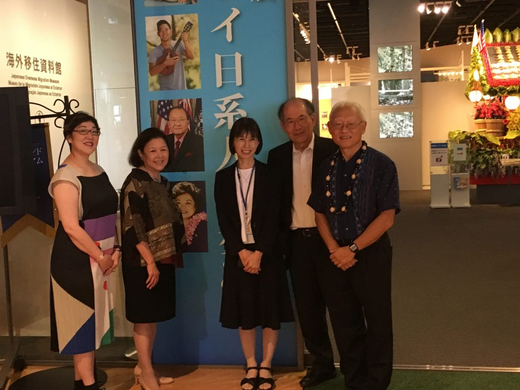 U.S.-Japan Council president Irene Hirano Inouye (second from left) is pictured next to the photograph of her late husband, U.S. Sen. Daniel Inouye, at the Japanese Overseas Migration Museum showing in Yokohama. Also pictured is Byrnes Yamashita (far right).