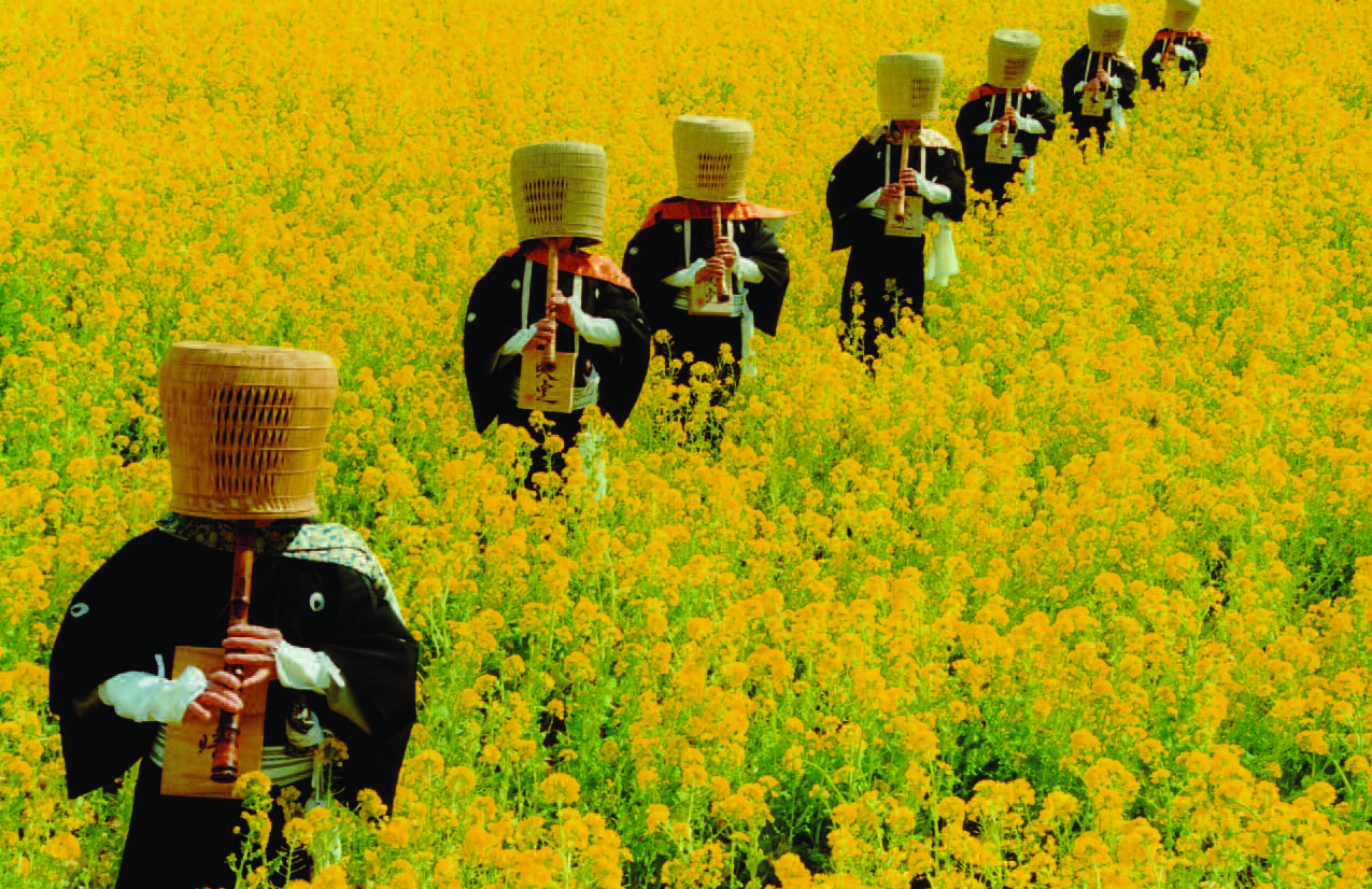 Priests in training play their shakuhachi while walking in a golden field of flowers. The priests' heads are covered with a basket because they are still training to become priests and haven't yet been shaved. (Photo courtesy East-West Center)