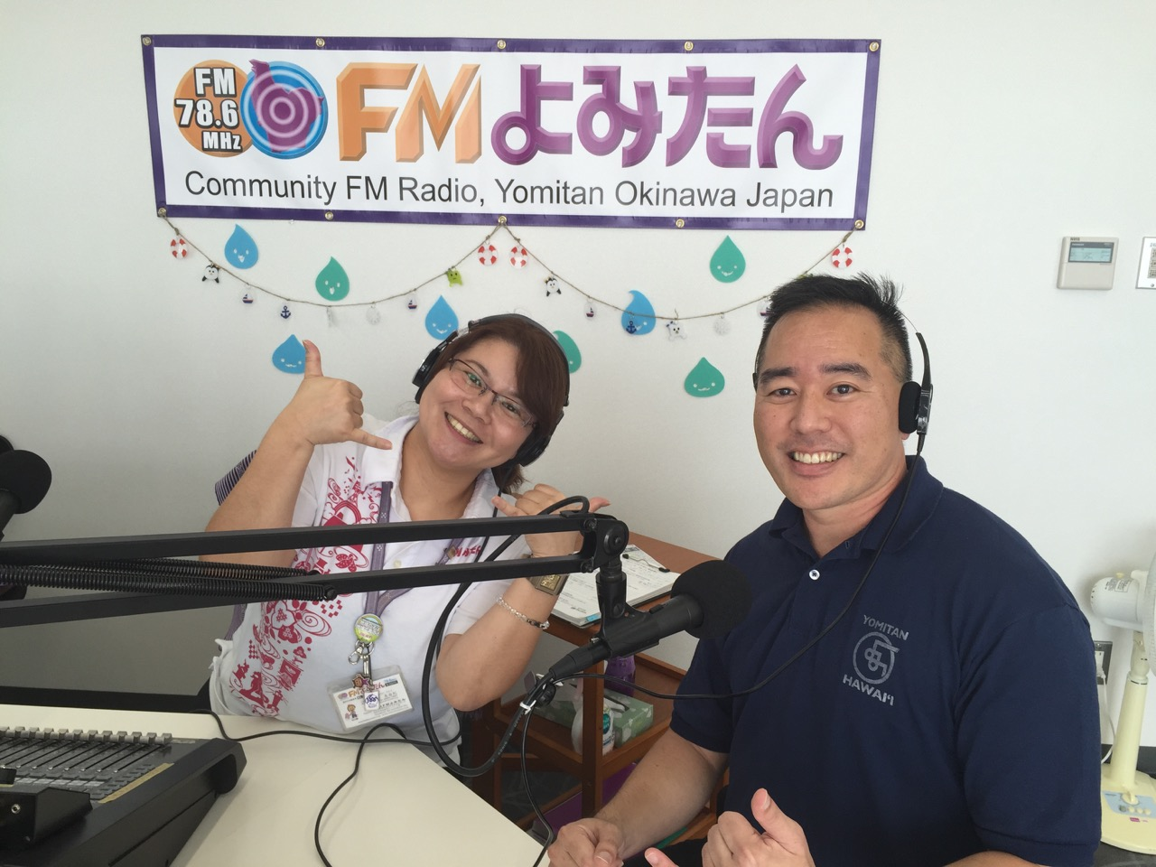 FM Yomitan announcer Miyuki Higa and guest Colin Sewake flash shakas during their broadcast.