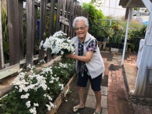 Mildred working in her yard, where she raises plants, flowers and vegetables. She is shown here with a bunch of mums she nurtured.