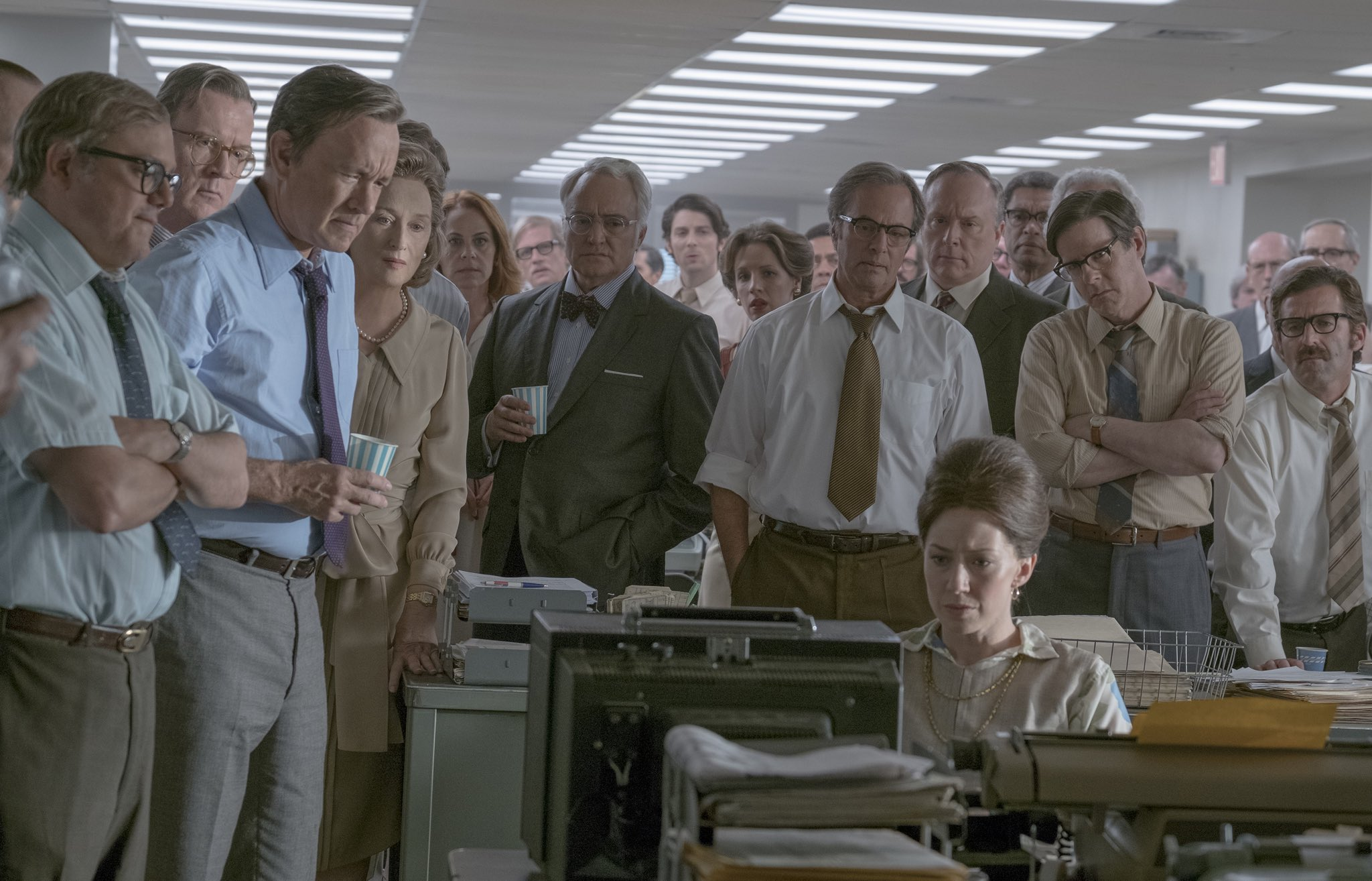 "Group photo of staff surrounding a woman's desk on the set of new movie, ""The Post"" (Photos courtesy 20th Century Fox)"