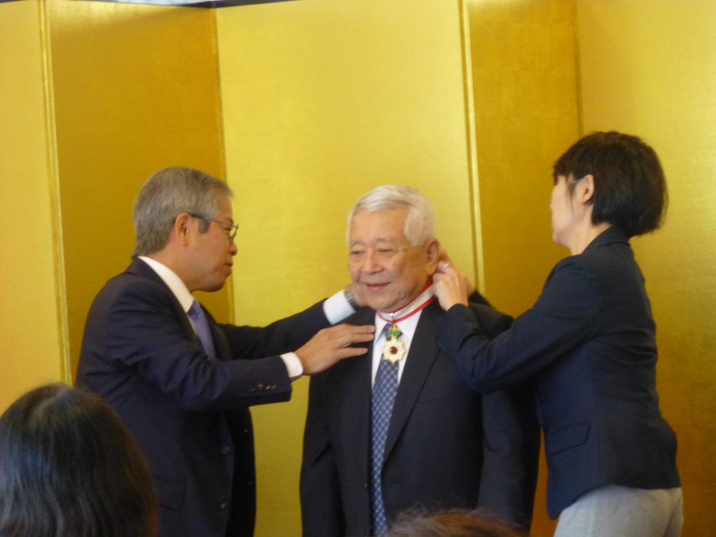Consul General Koichi Ito, assisted by Consulate staff member Susan Yamashita, places the Imperial Decoration around Dr. Izutsu's neck.