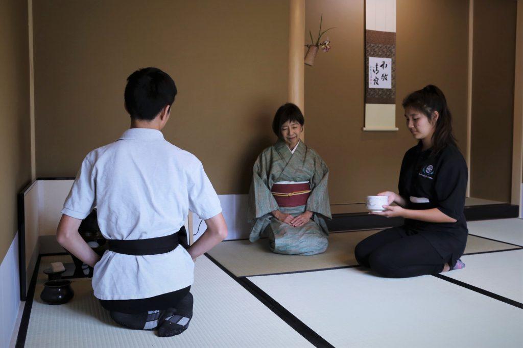 Pacific Buddhist Academy students Kano Hashimoto (right) and Yuma Sky Tochika practice chadö under the watchful eye of Marion Yasui-Sensei (in kimono). (Photos by Alan Kubota/Courtesy PBA)