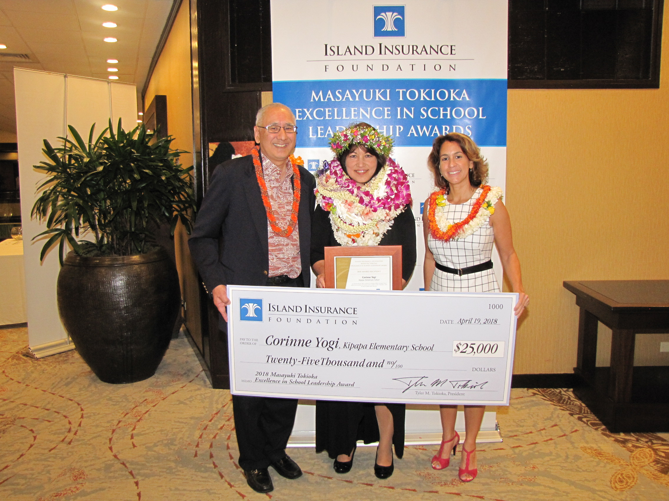 Island Insurance Foundation president Tyler Tokioka and state Department of Education Superintendent Christina Kishimoto (far right) congratulate 2018 Masayuki Tokioka Excellence in School Leadership Award recipient Corinne Yogi. (Photo courtesy DOE)