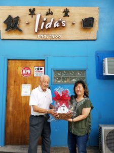 Third prize winner Michio Ohki (left) receives a gift basket from Iida's store manager, Shirley Iida.