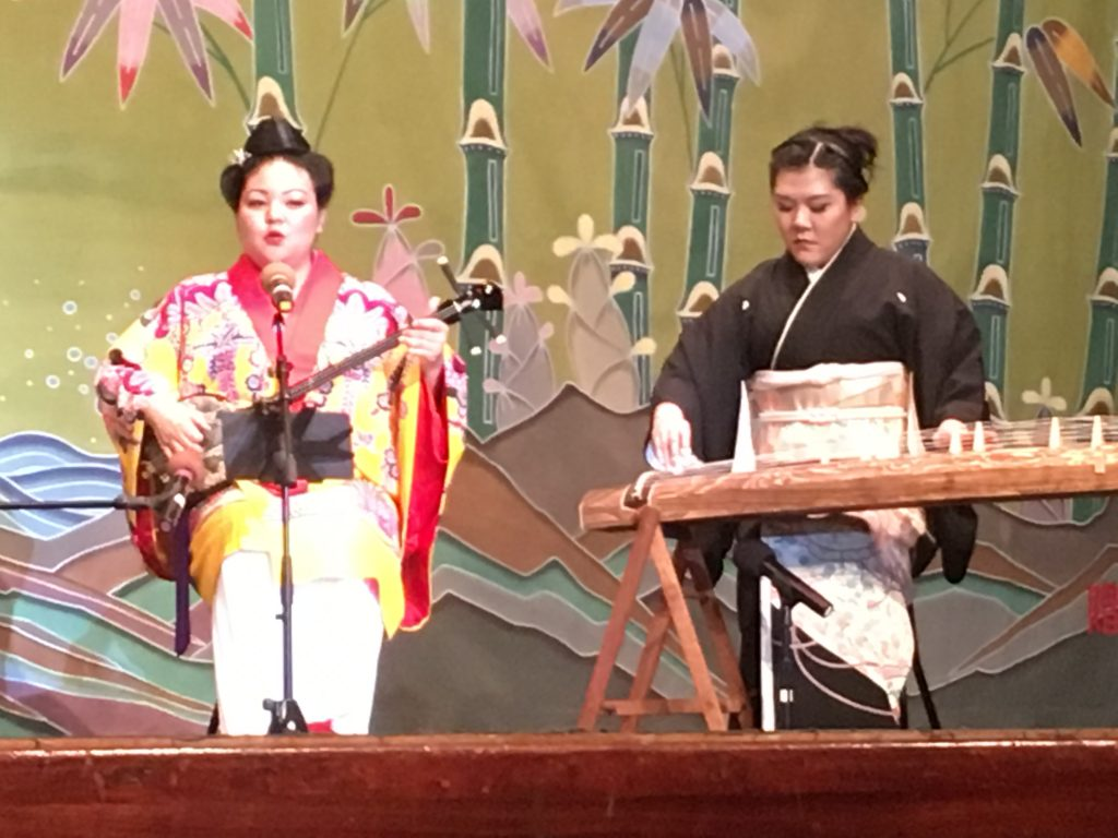 "Courtney Takara studies koto with Miyashiro Soho Kai and sanshin with Ryukyu Koten Afuso Ryu Ongaku Kenkyu Choichi Kai USA Hawaii in her ""free time."" Here, she performs an uta-sanshin (singing while playing sanshin) rendition of ""Tinsagu nu Hana"" with Sara Nakatsu, a shihan, or instructor, with Miyashiro Soho Kai."