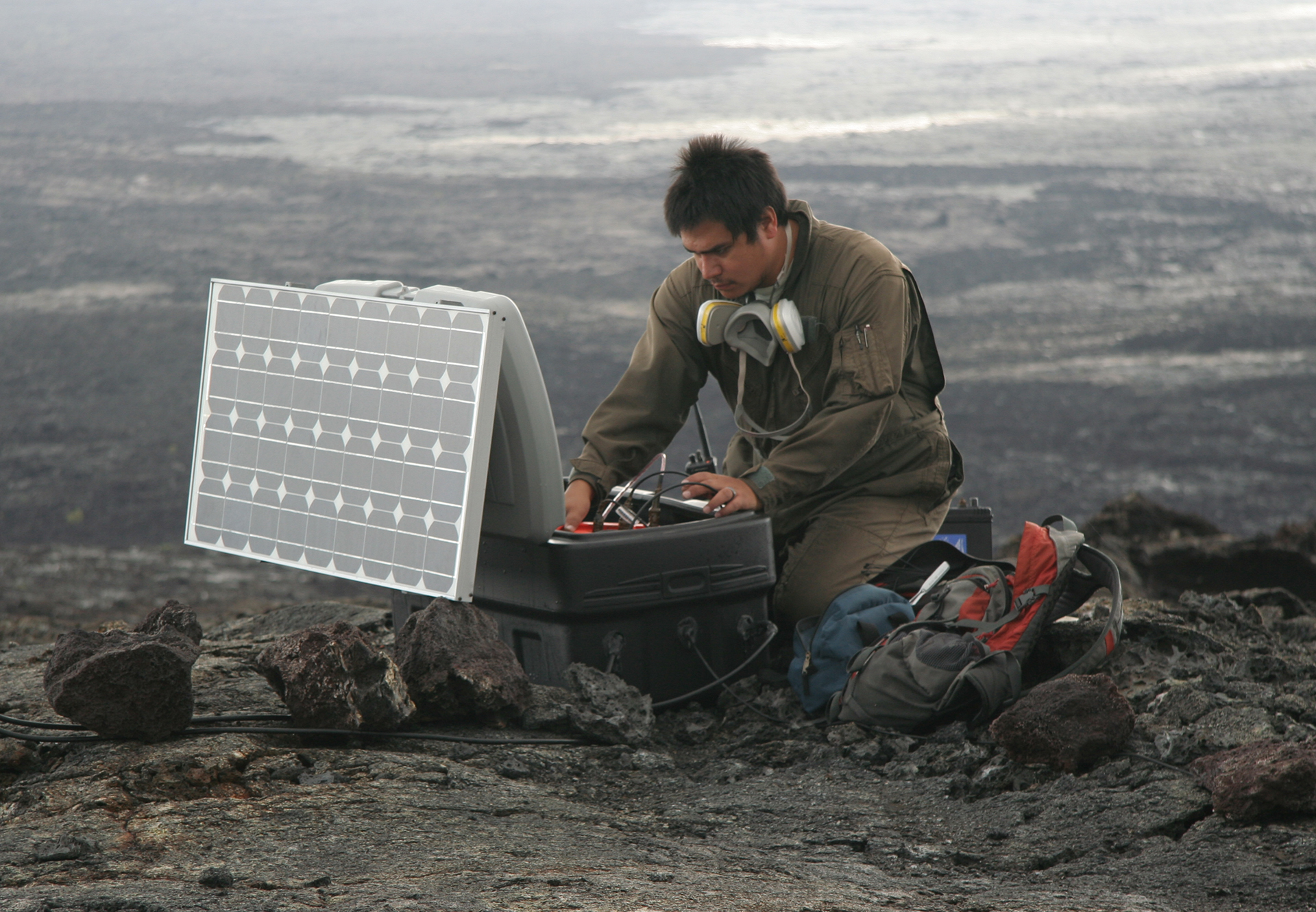 Kevan Kamibayashi testing equipment in a lava field.