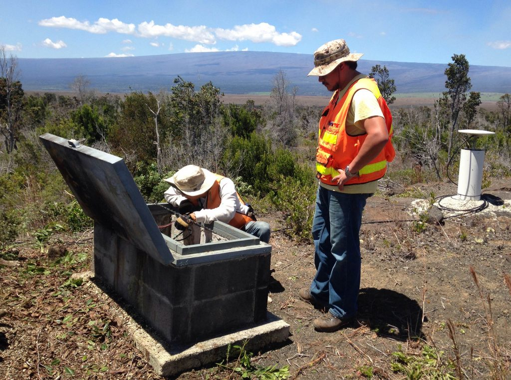 With Mauna Loa looming in the distance, Kevin Kamibayashi and a co-worker test equipment in the field.º