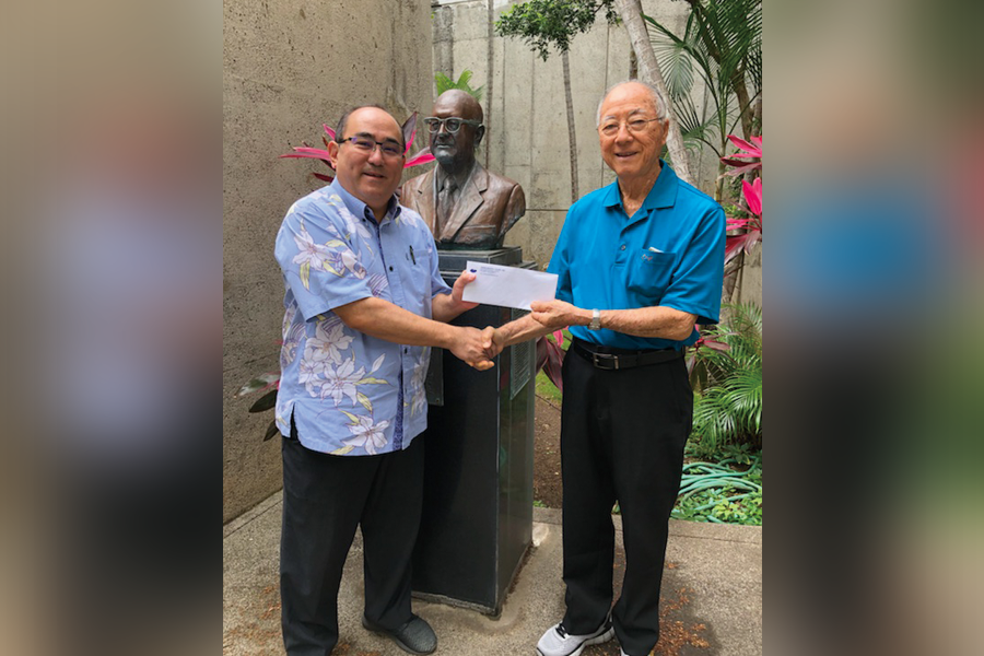 First prize winner Eric Kira (right) receives his prize from Grant Murata, Hawaii Herald/Hawaii Hochi advertising manager, on behalf of TransPacific Tours.