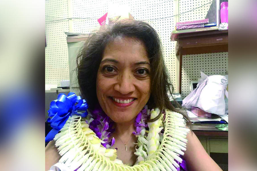 Photo of Gwen Battad Ishikawa with leis on her last day at the Hawaii Herald