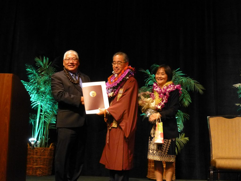 Hawaii Kyodan president Pieper Toyama presents a certificate to Bishop Eric Matsumoto, recognizing his 25 years of ministerial service to Honpa Hongwanji Mission of Hawaii. Matsumoto's wife Tamayo looks on.