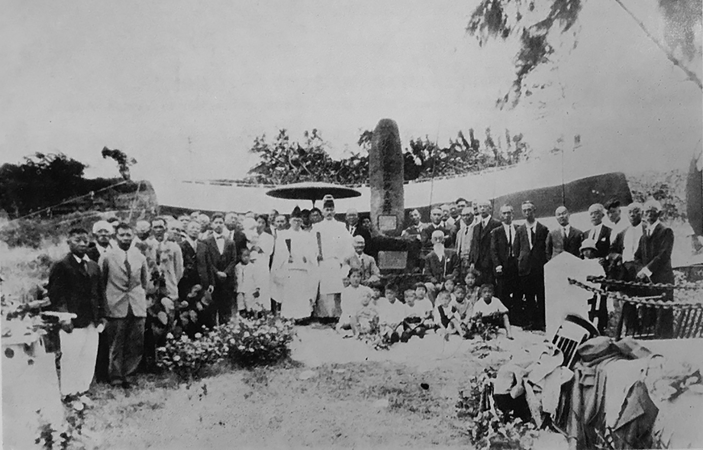 """The last two surviving Gannenmono in Hawai'i — Hanzo Tanagawa (seated left of the monument) and a full-bearded Sentaro Ishii (seated right of the monument) — attended the unveiling of the Makiki Cemetery monument playing homage to the Gannenmono in 1927. (From the book, """"A History of the Japanese Immigrants of Hawaii"""" by United Japanese Society of Hawaii."""")"""
