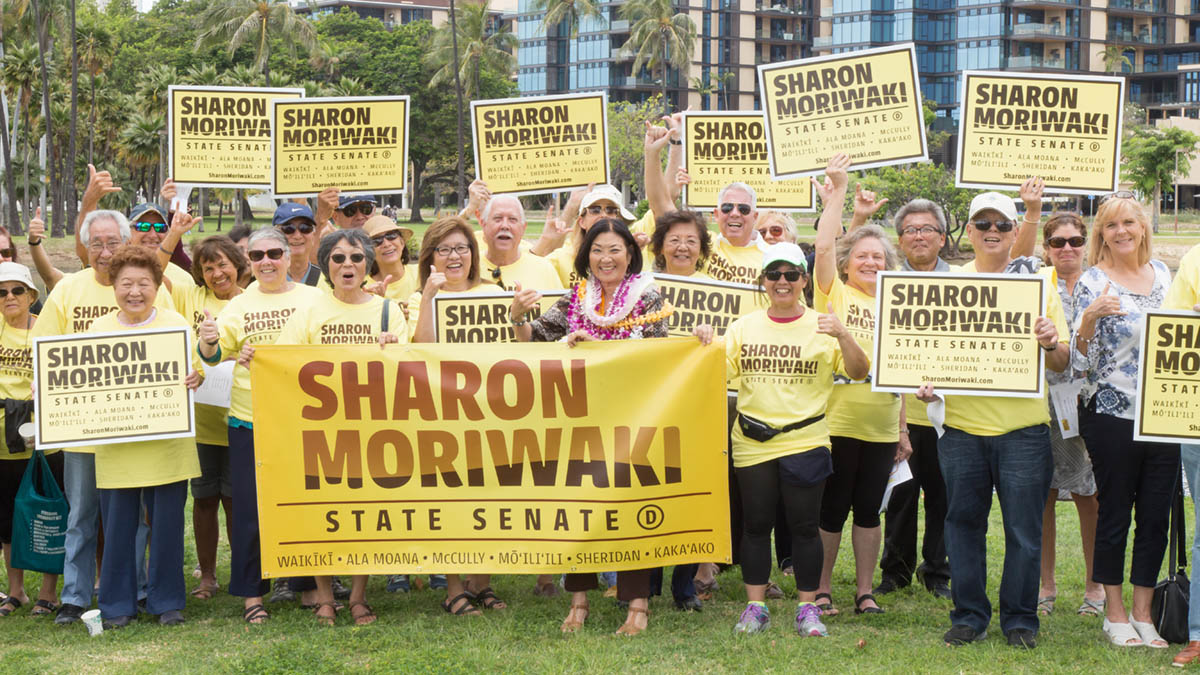 Group photo of campaign supporters holding signs featuring 'Sharon Moriwaki' with Democratic Candidate, Sharon Moriwaki