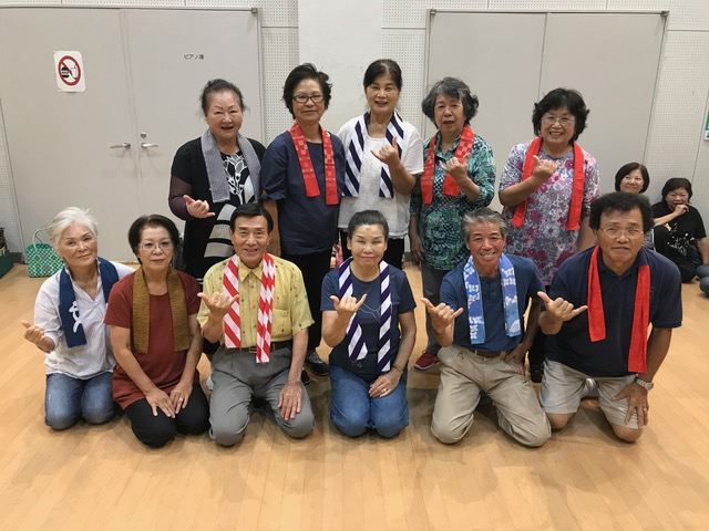The Yuibuyou Yomitan Group Ashibi members practice their shaka after dance practice. Okinawa-Hawaii Kyoukai member Masaji Matsuda is kneeling in the first row, far right. (Photos by Colin Sewake)