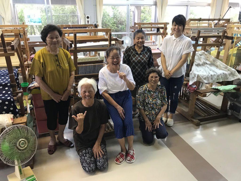 Matayoshi (center, seated), practicing her shaka, and a few of the weavers in Yomitan Hanaui's Namihira studio.