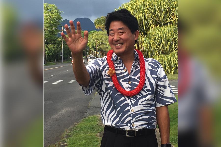 Democratic Candidate, Dale Kobayashi, alongside a busy road waving with a red lei and Aloha Shirt