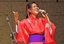 Photo of singer, Allison Arakawa, singing in a bright red kimono, mic in hand