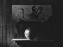 Dark black and white photo of a vase with a board featuring Japanese characters above it, on behalf of the Zen Ken Sho Art Show and Sale