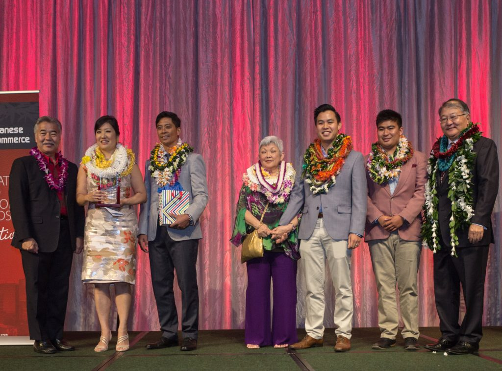 Gov. David Ige (far left) and outgoing HJCC chair Brian Nishida (far right) with the Nakamoto family. From left: Celeste and Larry Farinas, June Nakamoto, and Reece and Beau Farinas.
