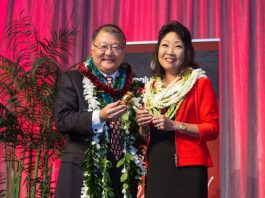 Outgoing HJCC chair, Brian Nishida presents the chair's gavel to his successor, Melanie Okazaki.
