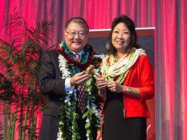 Outgoing HJCC chair, Brian Nishida presents the chair's gavel to his successor, Melanie Okazaki.