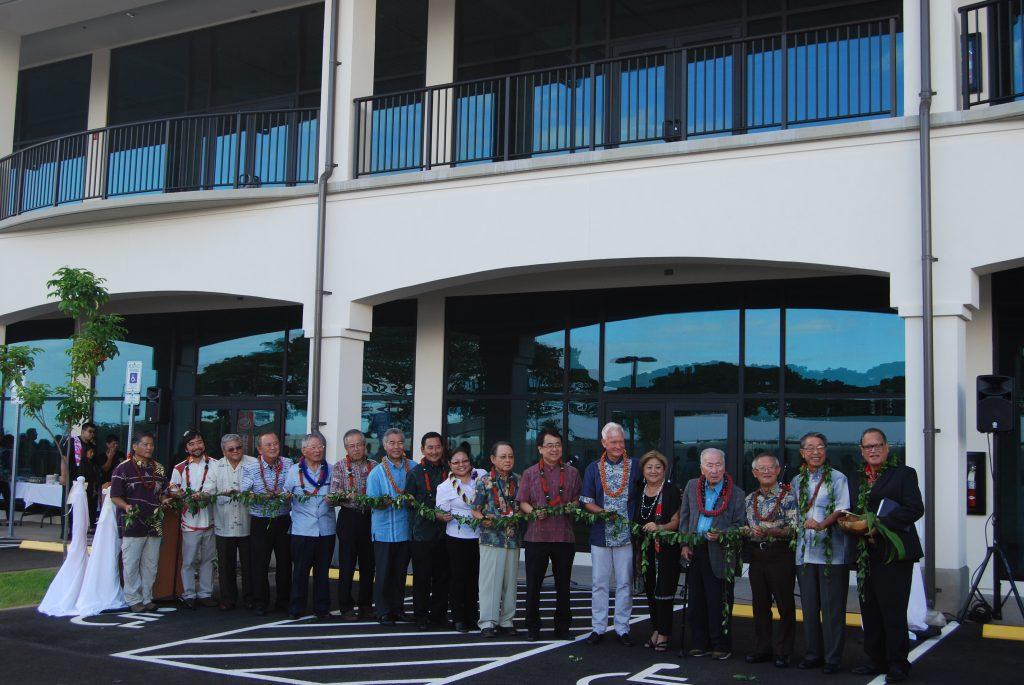 HUOA officials gathered with their Okinawa supporters to formally dedicate and open the Hawaii Okinawa Plaza. From left: past presidents Jon Itomura, Mark Higa (project co-chair), Ford Chinen and Maurice Yamasato (project architect); Choko Takayama of the Okinawa Hawaii Kyokai; Consul General of Japan Koichi Ito; Gov. David Ige; past president Chris Shimabukuro (project co-chair); HUOA 2018 president Courtney Takara; Okinawa fundraising chair Asami Ginoza; Takao Kadekaru, representing the Okinawa Prefectural Government; Mayor Kirk Caldwell; HUOA president-elect Jocelyn Ige; Okinawa Hawaii Kyokai member Akira Makiya; past presidents Ryokichi Higashionna and George Tamashiro; and Kahu Kelekona Bishaw. (Not pictured: the Rev. Shindo Nishiyama) (Photo by Noriyoshi Kanaizumi)