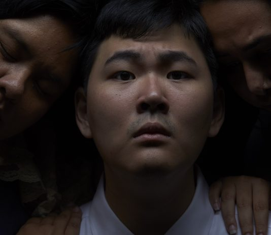 """In this scene from """"A Walking Shadow,"""" Myles Fukunaga, played by Alaka'i Cunningham, is comforted by his family, played by Juvy Lucina and Daphnei Hussein. (WCC photo by Orrin Nakanelua)"""