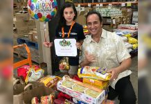 Ron Mizutani, President and CEO of Hawaii Food Bank, along side a young girl, storing bags of food on a flat bed