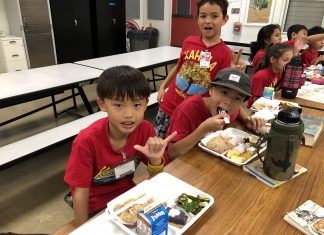 Kahala Elementary School third-graders (front, from left) Alex Tomasa, Levi-Michael Bird and (standing) Hi'ilei Dunn enjoying their Thanksgiving lunch.