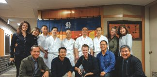 """The """"Family Ingredients"""" crew with Chef Jiro Ono outside his Tökyö restaurant: Kneeling, from left: Chef Ed Kenney, producer Dan Nakasone, cinematographer Todd Fink, director Ty Sanga and Chef Alan Wong. Back row, from left: director of photography Renea Veneri Stewart, executive producer Heather Giugni, Jiro's apprentices in whites with chefs Jiro-san and Yoshikazu-san (fifth and sixth from left), Japan coordinator Nancy Singleton Hachisu and Leigh Ito, vice president, Alan Wong's Restaurants. Missing from photo: sound engineer John Saimo. (Photos courtesy Dan Nakasone)"""
