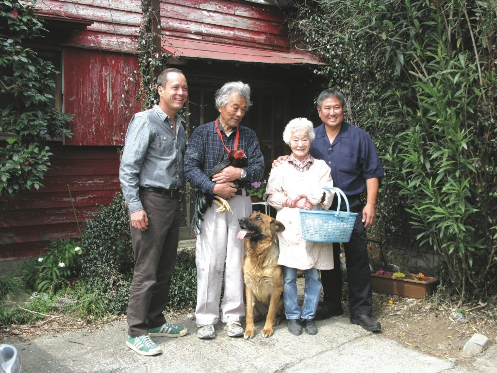 Yoshishito Asano, carrying a Shamo rooster, and his wife Toshiko with their loyal German Shepherd, Cherry, at their sides with show host and chef Ed Kenney (left) and Chef Alan Wong.