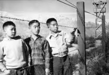 Black and white photo of three Japanese American boys in Manzanar Relocation Center by Prolific California Photographer, Toyo Miyatake