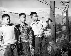 Black and white photo of three Japanese American boys in Manzanar Relocation Center by Prolific California Photographer, Toyo Miyatake